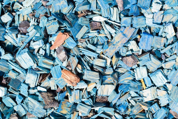 Blue decorative chips, wood textured background top view. shredded tree bark for decorating a garden plot and other surfaces, close-up