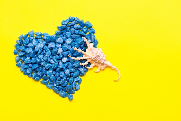 Blue decorative stones laid out in the shape of a heart and a seashell on a yellow background