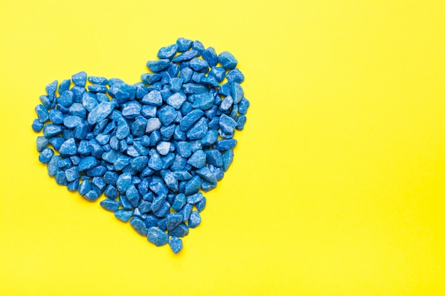 Blue decorative stones laid out in the shape of a heart on a yellow background