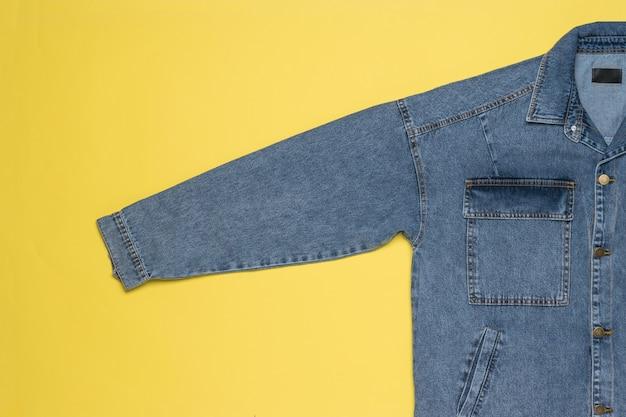 Синяя джинсовая куртка с удлиненным рукавом на желтом фоне. популярная повседневная одежда.