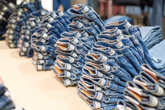 モダンなショッピングモールの衣料品店の上部にある木製のテーブルに青いデニムジーンズが積み重なっています