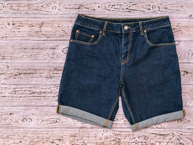 Blue denim shorts on a tinted pink wooden surface