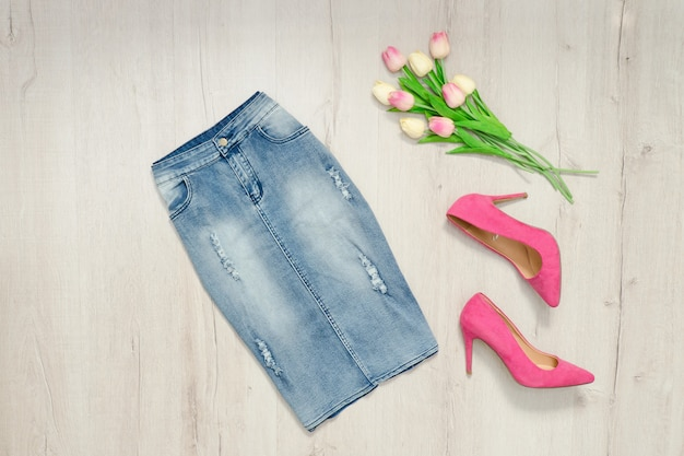 Blue denim skirt, pink shoes and bouquet of tulips. fashionable