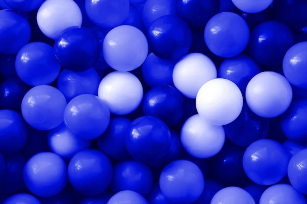 青いデザイナーの背景。子供の遊び場で楽しくジャンプするための多くの青いボール。閉じる。子供の休日の背景。子供の誕生日。