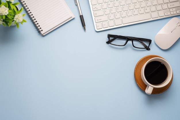 ブルーデスクミニマルスタイルコーヒーグラスノートブックキーボードコピースペース。