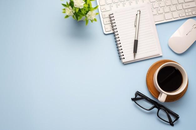Синий стол минимальный стиль с кофе очки ноутбук клавиатура копирование пространства.