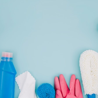 Синяя бутылка моющего средства; салфетка; губка; розовые перчатки на синем фоне