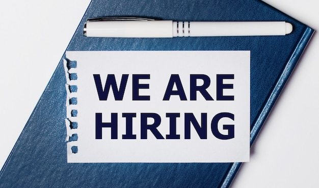 The blue diary lies on a light background. on has a white pen and a piece of paper with the text we are hiring.