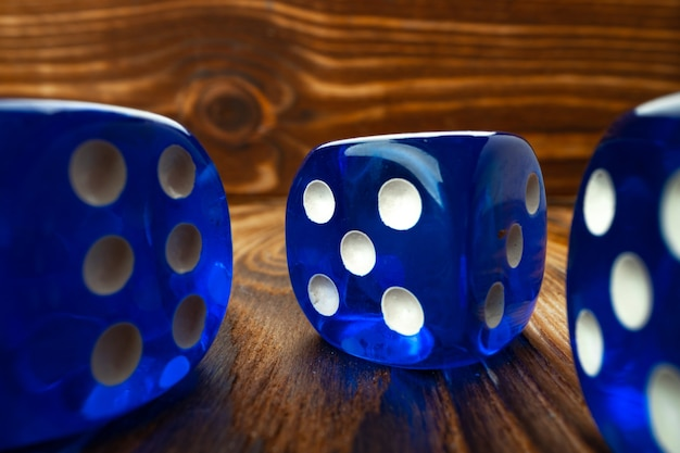 Blue dice cubes against brown wooden background close up photo
