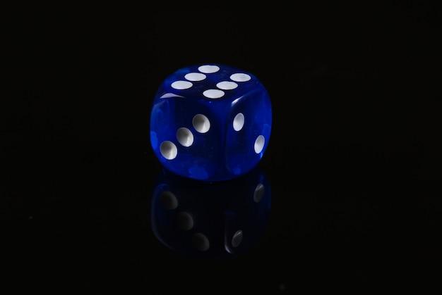 검은 색 표면에 파란색 주사위입니다. 게임 중독. 운