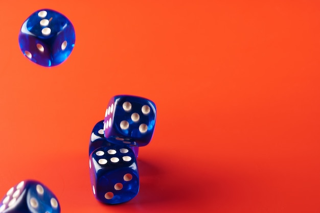 Blue dice on red background close up