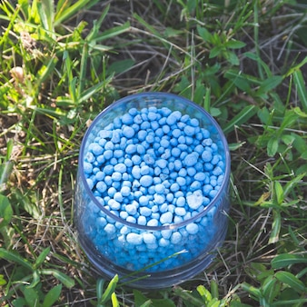 Blue different shape chemical fertilizer granules in glass on green grass
