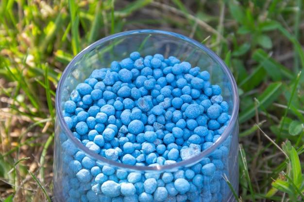 Голубые гранулы химического удобрения различной формы в стекле на зеленой траве