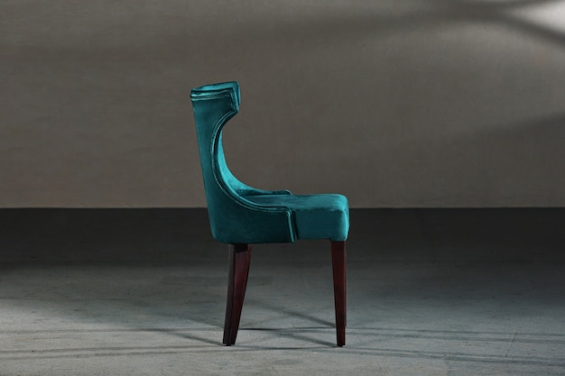 Blue dining room chair in a studio with gray walls