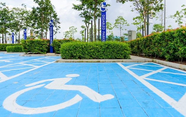 Blue disabled parking sign in the car park area.