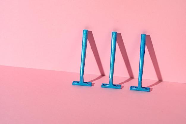ピンクの紙の背景に青い使い捨てかみそり