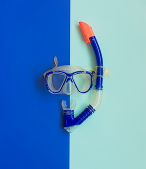 Blue diving mask and snorkel on blue. diving equipment.