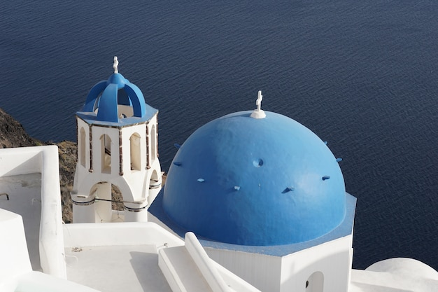 Blue dome church and whitewashed building in oia, santorini, greece