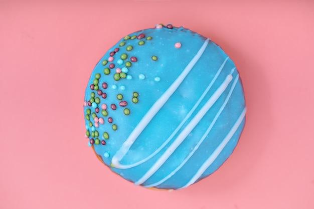 Синий пончик на розовом фоне. концепция минимализма, цвет игры. розовый фон