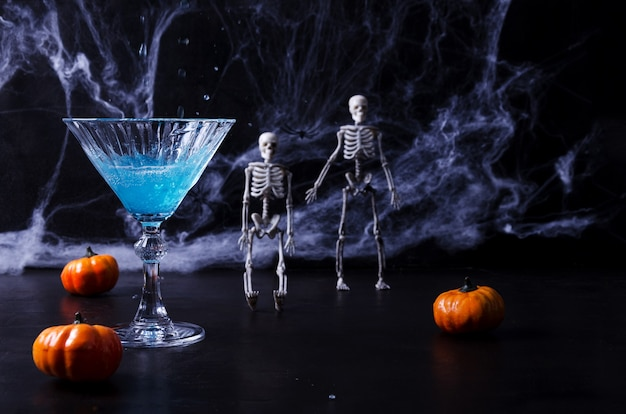 ハロウィーンの青い飲み物、クモの巣、スケルトン、カボチャの背景に、黒い背景のディアデムルトス