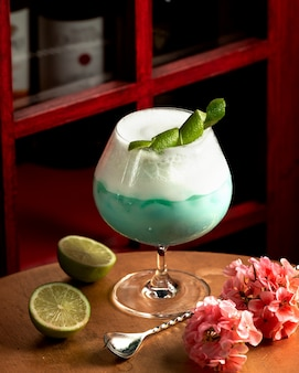 Blue drink with foam decorated with lemon peel