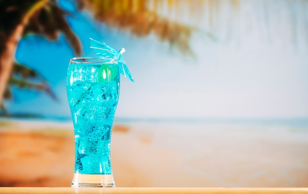 Blue drink with ice cubes in long umbrella decorated glass