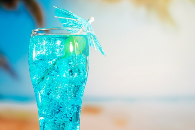 Blue drink with ice cubes in umbrella decorated glass