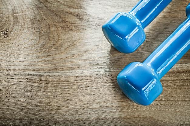 木の板のフィットネスの概念に青いダンベルの重み