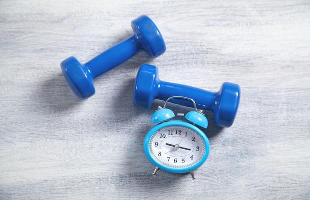 白い木製の背景に青いダンベルと目覚まし時計。