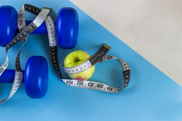 Blue dumbbells, measuring tape and apple on a blue background. cares about the body.