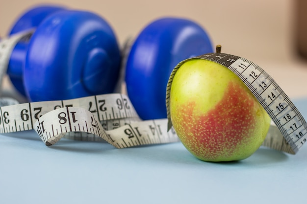 Blue dumbbells, measuring tape and apple on a blue background. healthy lifestyle