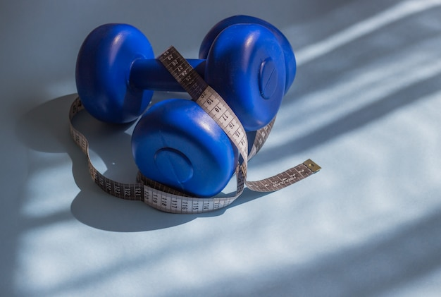 Blue dumbbells, tape measure on a blue background in the sun. healthy lifestyle