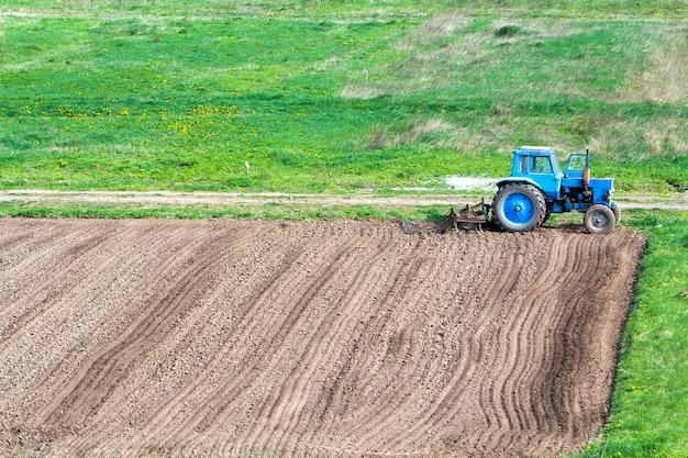Синий пыльный трактор с рыхлителем посевной, стоящим на краю свеже вспаханного и возделанного поля, подготовленной к посеву почвы. концепция сельского хозяйства, сельского хозяйства и сельскохозяйственной техники.