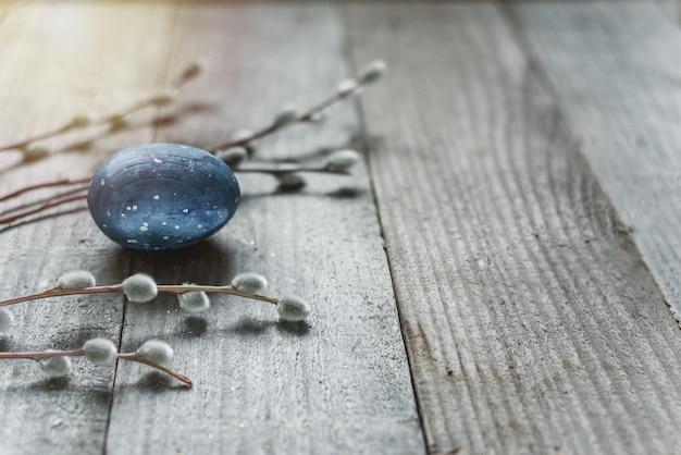 Голубое пасхальное яйцо и ветви вербы киски на деревянном столе.