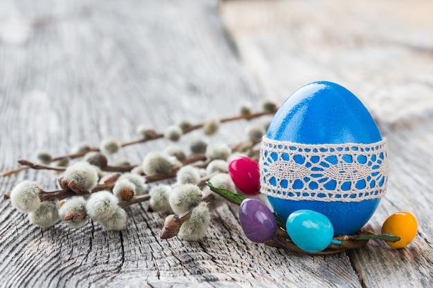 Голубое пасхальное яйцо, украшенное кружевом и ветвью ивы на деревянной стене. выборочный фокус, копия