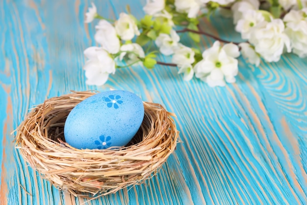 짚 둥지와 텍스트에 대 한 공간을 가진 푸른 나무 배경에 꽃 지점에 파란색 부활절 달걀.