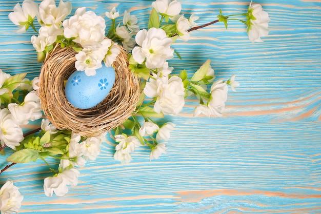 짚 둥지와 푸른 나무 테이블에 꽃 지점에 파란색 부활절 달걀. 평면도, 평면 누워.