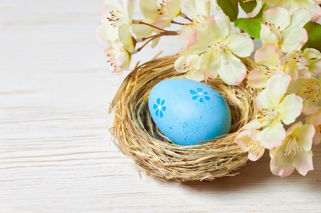 밀 짚 둥지 및 지점에 파란색 부활절 달걀