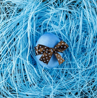 Blue easter egg with brown bow on blue background