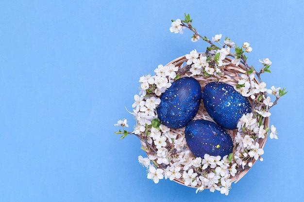 Синие пасхальные яйца в корзине с цветами на синем фоне.