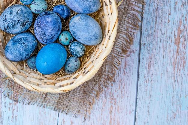 Синие пасхальные яйца в деревенском природном стиле яйца в гнезде из сена в плетеной корзине на мешковине