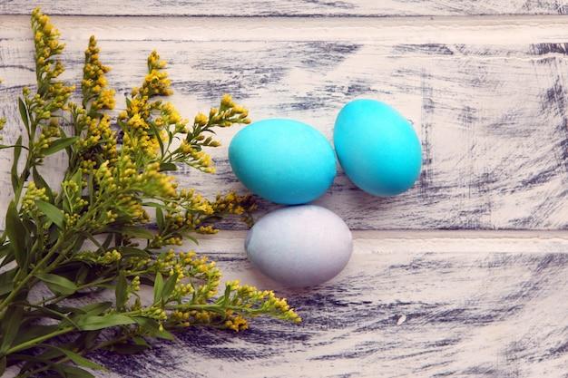 白い塗られた木製のテーブルの背景に青いイースターエッグ。デザインテンプレート、コピースペース。カラフルなイースターエッグ。イースター休暇のコンセプト、卵のパターン、連続してカラフル、白い背景。