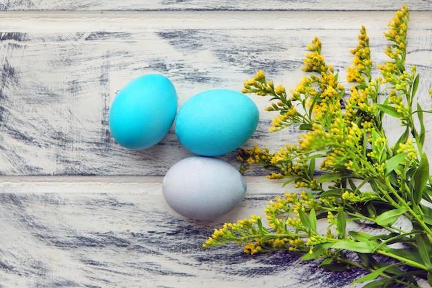 白い塗られた木製のテーブルの背景に青いイースターエッグ。デザインテンプレート、空きコピースペース。カラフルなイースターエッグ。イースター休暇のコンセプト、卵のパターン、連続してカラフル、白い背景。
