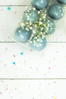 Blue easter eggs on a white table among bouquets of gypsophila