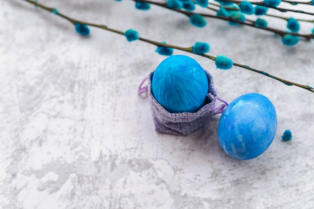 Blue easter eggs with decorative bag and willow twigs