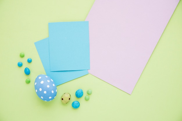 Blue easter eggs with paper sheets on green table