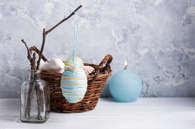 Свеча горит голубым яйцом в деревенской пасхальной композиции на белом деревянном столе