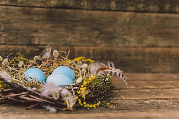 깃털이 있는 둥지에 있는 파란 계란. 보드의 배경. 부활절 개념입니다.