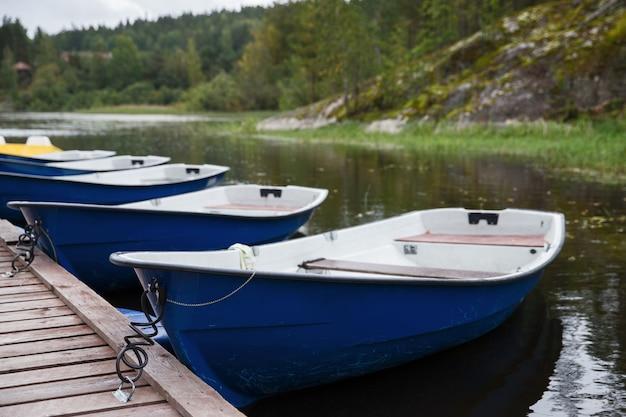 木製の桟橋のクローズアップ、曇りの秋の空、背景の森に沿って湖の青い空のボート