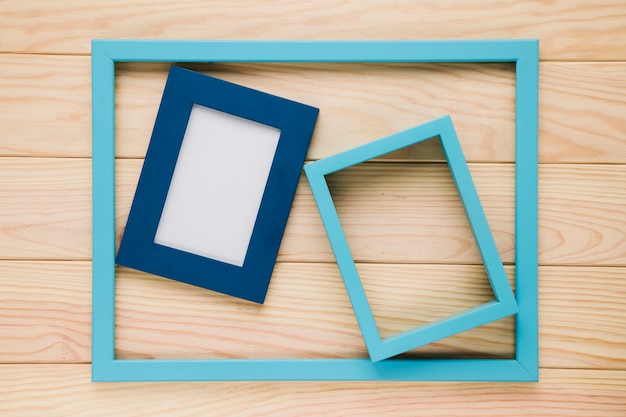Blue empty frames on wooden background